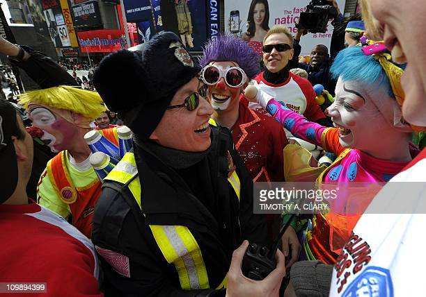 Clowns from the Ringling Bros and Barnum Bailey Clown Alley gather around a security guard as they perform in Times Square March 9 2011 as clowns and...