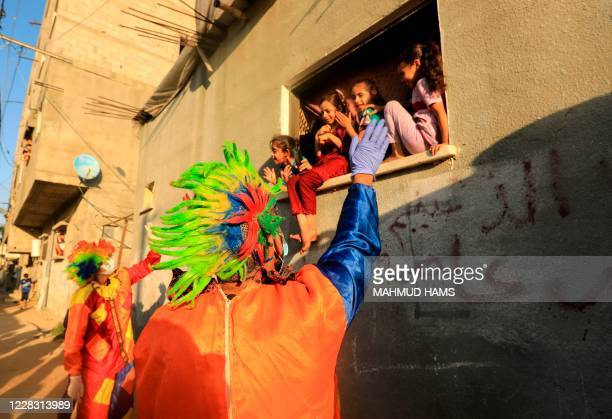 Clowns perform to entertain Palestinian children during a lockdown imposed by the local authorities following a surge in coronavirus cases, in Khan...