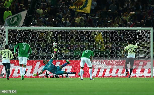 Club America's forward Oribe Peralta scores a penalty as Atletico Nacional goalkeeper Franco Armani jumps during the Club World Cup football match...