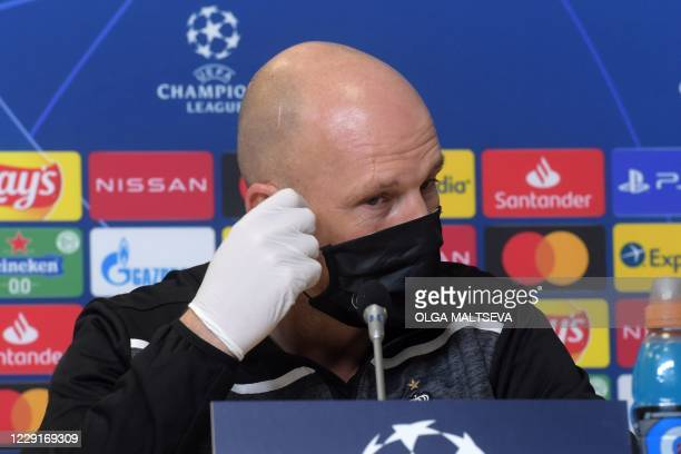 Club Brugge's Belgian coach Philippe Clement takes off his face mask during a press conference at the Saint Petersburg Stadium in Saint Petersburg on...