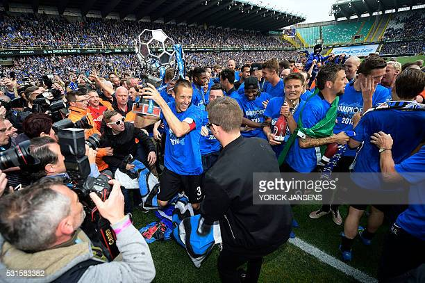 Club Brugge's defender Timmy Simons brandishes the trophy as he celebrates with his team after winning for the first time in 11 years the Belgian...