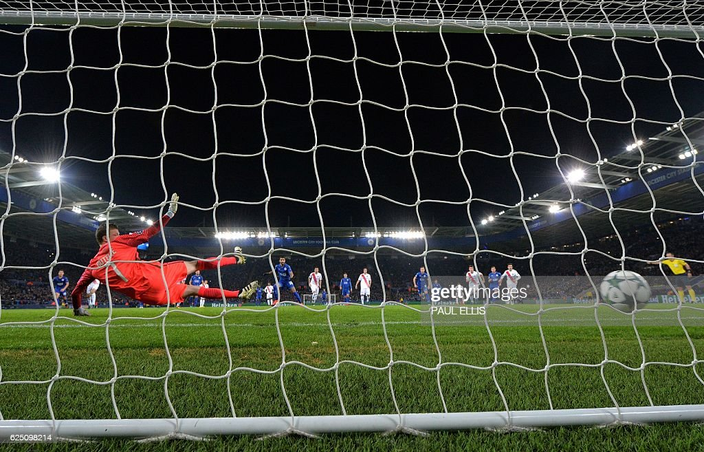 Club Brugge's French goalkeeper Ludovic Butelle (L) dives as Leicester City's Algerian midfielder Riyad Mahrez (C) scores his team's second goal from the penalty spot during the UEFA Champions League group G football match between Leicester City and Club Brugge at the King Power Stadium in Leicester, central England on November 22, 2016. Leicester won the match 2-1. / AFP / Paul ELLIS