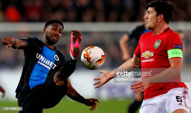 Club Brugge's Nigerian forward Dennis Emmanuel Bonaventure fights for the ball with Manchester United's English defender Harry Maguire during the...