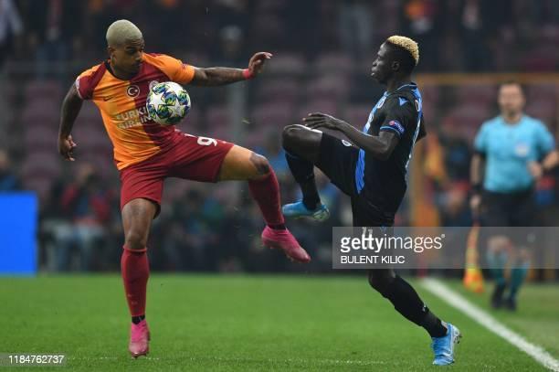 Club Brugge's Senegalese midfielder Krepin Diatta vies with Galatasaray's Turkish goalkeeper Boran Gungor during the UEFA Champions League football...