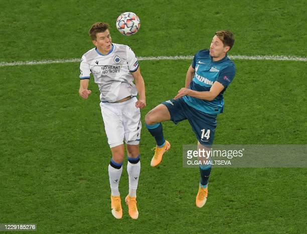Club Brugge's Ukrainian defender Eduard Sobol fights for the ball with Zenit St Petersburg's Russian midfielder Daler Kuzyaev during the UEFA...