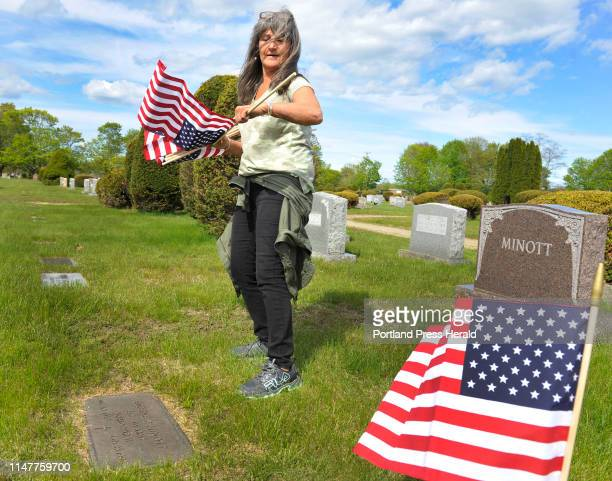VFW club members and volunteers place small American flag's on the grave sites of veterans at the Forest City cemetary in South Portland Margaret...