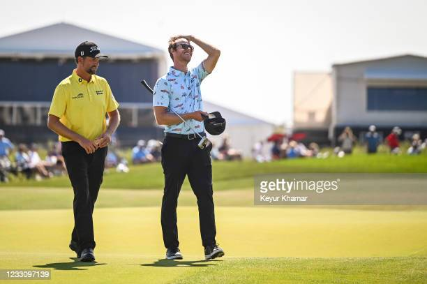 Club Professional Ben Cook smiles with Webb Simpson on the 18th hole green during the final round of the PGA Championship on The Ocean Course at...