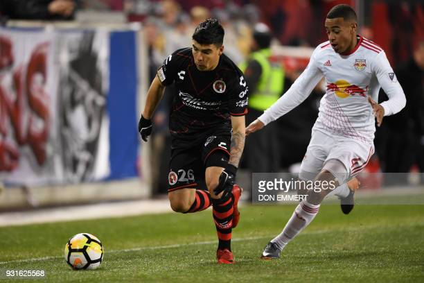 Club Tijuana's Luis Angel Mendoza and New York Red Bulls' Tyler Adams vie for the ball during the Concacaf Champions League 2nd Leg Quarterfinal...