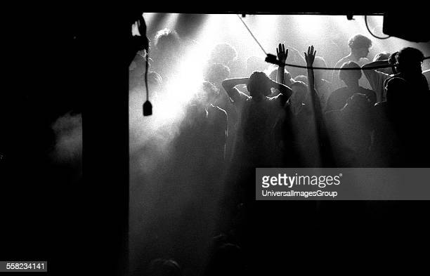 Clubber raises their hands on an atmospheric main stage during a break in the music at the Hacienda, Manchester 1988.