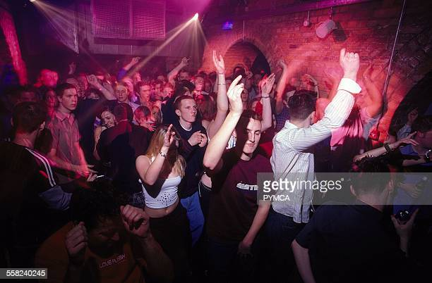Clubbers dancing with hands in the air at World DJ Day Fabric London March 2002.