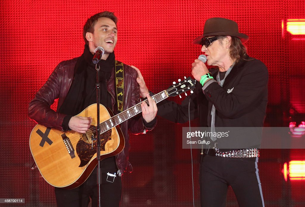 Clueso (L) and Udo Lindenberg performs at the Brandenburg Gate during celebrations on the 25th anniversary of the fall of the Berlin Wall on November 9, 2014 in Berlin, Germany. The city of Berlin is commemorating the 25th anniversary of the fall of the Berlin Wall with an installation of 6,800 lamps coupled with illuminated balloons along a 15km route where the Wall once ran and divided the city into capitalist West and communist East. The fall of the Wall on November 9, 1989, was among the most powerful symbols of the revolutions that swept through the communist countries of Eastern Europe and heralded the end of the Cold War. Built by the communist authorities of East Germany in 1961, the Wall prevented East Germans from fleeing west and was equipped with guard towers and deadly traps.