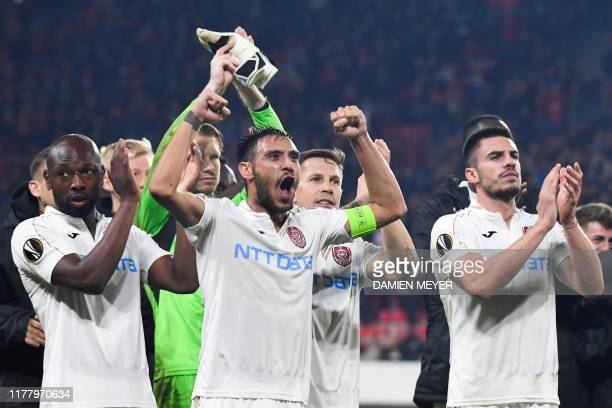 Cluj's Portuguese defender Camora celebrates with teammates after winning the Europa League Group E football match between Rennes and CFR Cluj at the...