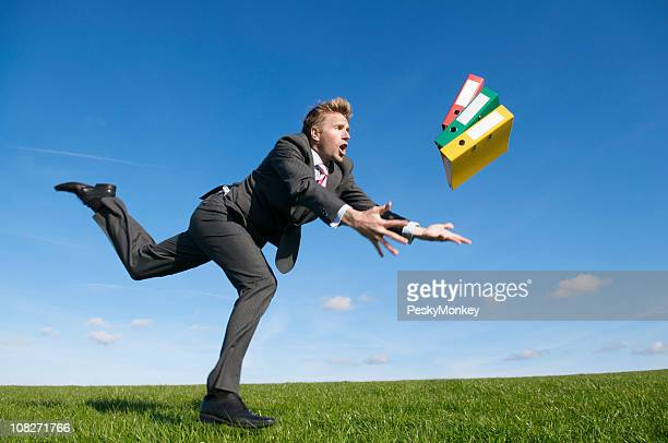 Clumsy Businessman Tripping Outdoors Dropping Handful of Binders