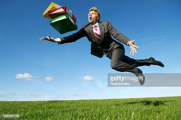 Clumsy Businessman Tripping with File Folders in Meadow