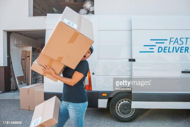 onhandige vrouwelijke werknemer die de dozen draagt - achteloos stockfoto's en -beelden