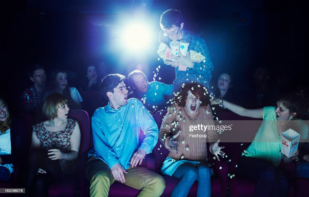 Clumsy guy spilling popcorn over woman : Stock Photo