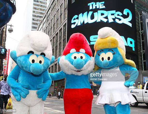 Clumsy Smurf Papa Smurf and Smurfette from the film The Smurfs 2' pose before ringing the opening bell at the NASDAQ MarketSite on July 25 2013 in...