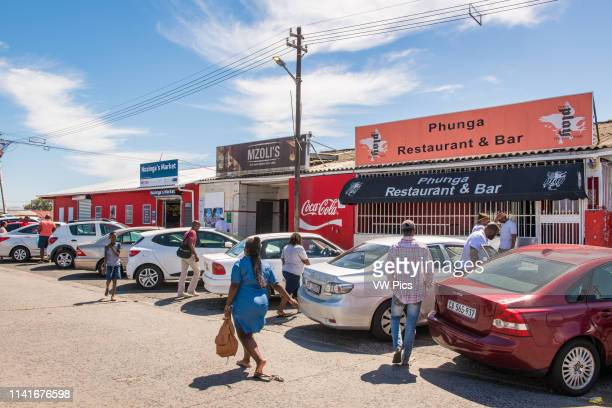 A cluster of cars sits outside local businesses as people mill about in Guguletu township in Cape Town South Africa