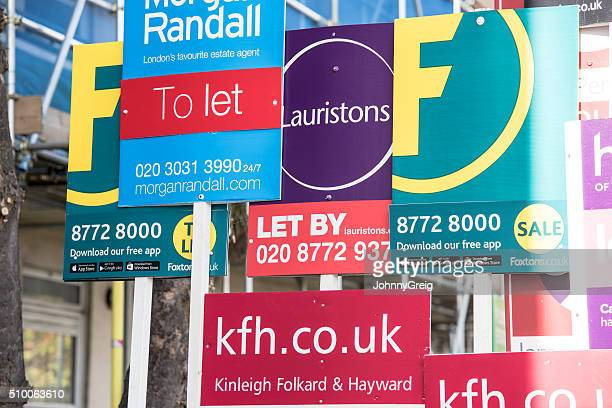 cluster of estate agent signs in london - house rental stock photos and pictures