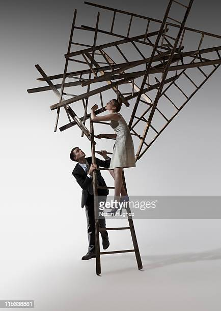 cluster of ladders falling on man and woman