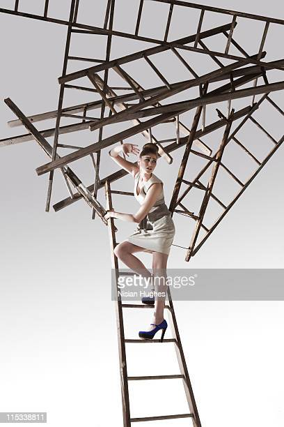 cluster of ladders falling onto business woman