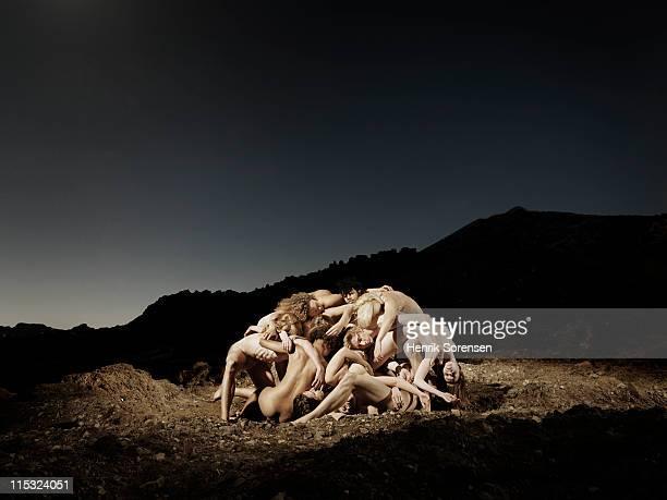 cluster of naked people in barren landscape
