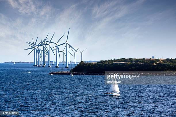 cluster of ocean wind turbines with sailboat in foreground - windenergie stockfoto's en -beelden