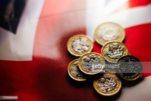 Cluster of one pound sterling coins sit on a British Union flag, also known as a Union Jack, in this arranged photograph in London, U.K., on...