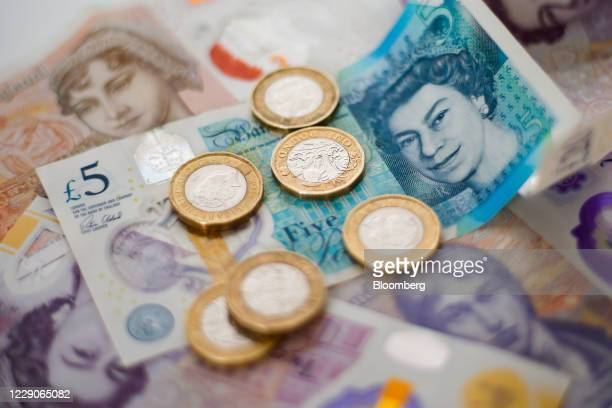 Cluster of one pound sterling coins stand on top of five, ten and twenty pound banknotes in this arranged photograph in London, U.K., on Wednesday,...