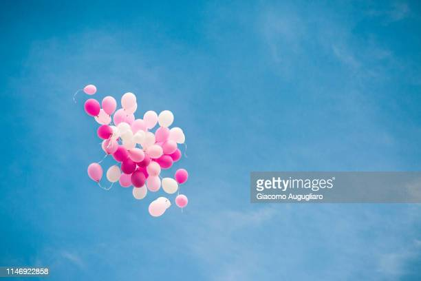 cluster of pink baloons for a girl baptism in the blue sky. italy - memorial event stock pictures, royalty-free photos & images