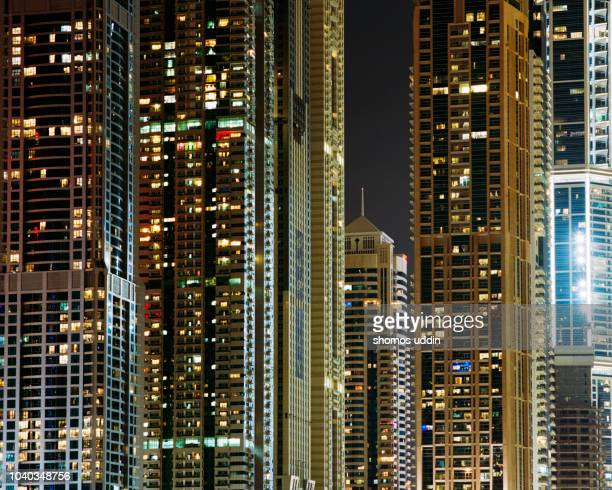 cluster of tower blocks lit up at night - persian gulf stock-fotos und bilder