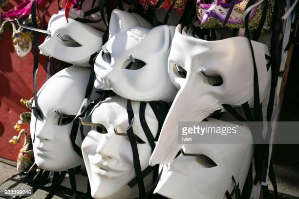 a cluster of venetian masks in a storefront window. - maschere veneziane foto e immagini stock