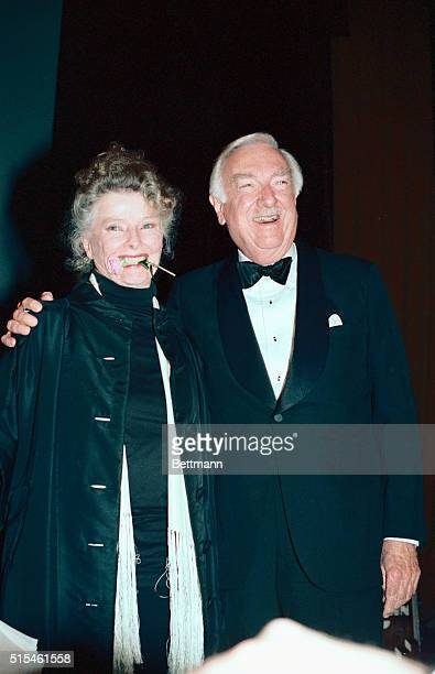 Clutching a rose that Walter Cronkite gave her in her teeth Katharine Hepburn smiles for the crowd after the dual tribute to herself and her mother...