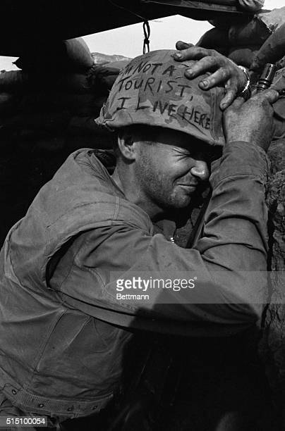 Clutching helmet and weapon Marine L/Cpl James Jones of Pensacola Florida winces as Communist mortar rounds fly overhead during enemy shelling of...