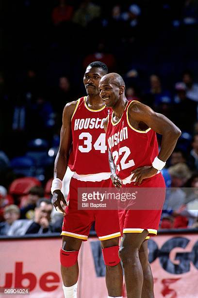 Clyde Drexler and Hakeem Olajuwon of the Houston Rockets enjoy a light moment against the Washington Bullets during an NBA game at the Capital Centre...
