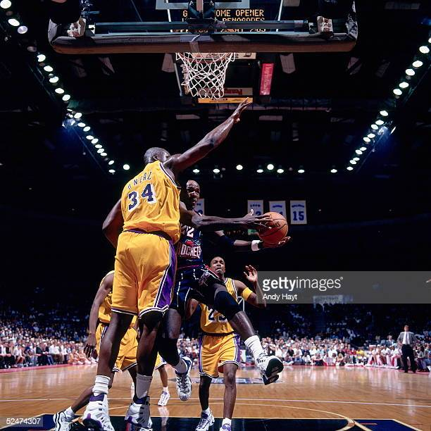 Clyde Drexler of the Houston Rockets drives to the basket against Shaquille O'Neal of the Los Angeles Lakers during an NBA game on October 22 1996 in...