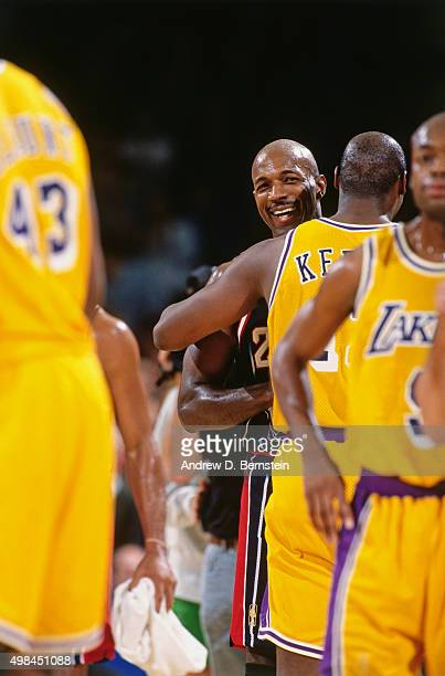 Clyde Drexler of the Houston Rockets hugs Jerome Kersey of the Los Angeles Lakers on November 24 1996 at the Great Western Forum in Inglewood...
