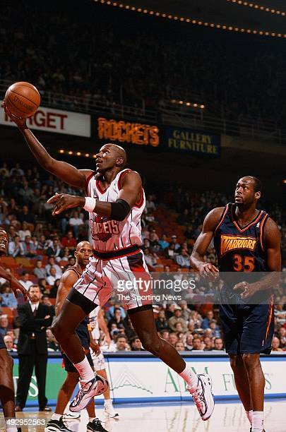 Clyde Drexler of the Houston Rockets lays the ball up past Erick Dampier of the Golden State Warriors during the game on November 22 1997 at the...