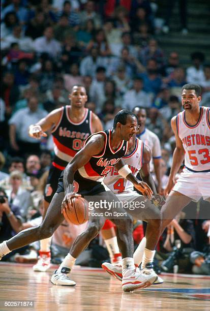 Clyde Drexler of the Portland Trail Blazers dribbles the ball against the Detroit Pistons during an NBA basketball game circa 1990 at The Palace of...