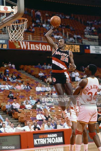 Clyde Drexler of the Portland Trail Blazers goes up for a slam dunk against the Houston Rockets during an NBA game at the Summit circa 1990 in...
