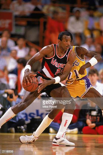 Clyde Drexler of the Portland Trail Blazers is defended by Michael Cooper of the Los Angeles Lakers during the 19871988 NBA season game at the Great...