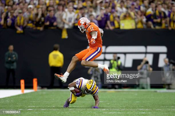 Clyde EdwardsHelaire of the LSU Tigers catches the ball as Isaiah Simmons of the Clemson Tigers defends in the College Football Playoff National...