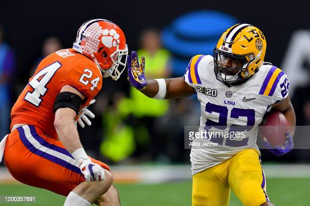 Clyde EdwardsHelaire of the LSU Tigers gives Nolan Turner of the Clemson Tigers a stiff arm during the fourth quarter of the College Football Playoff...