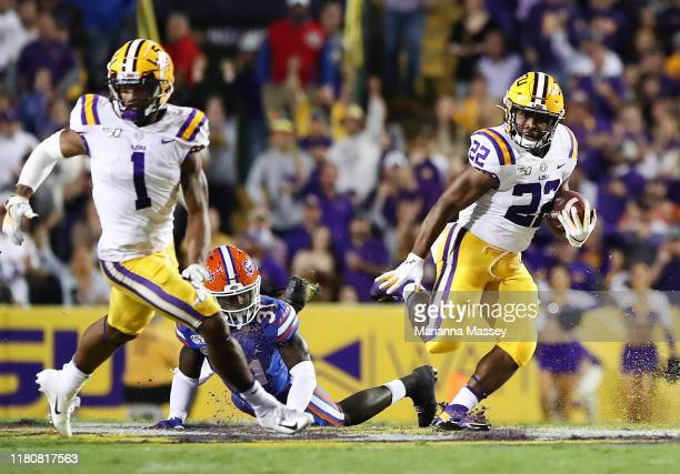 Clyde EdwardsHelaire of the LSU Tigers runs the ball for a first down as Ja'Marr Chase of the LSU Tigers looks on against the Florida Gators at Tiger...