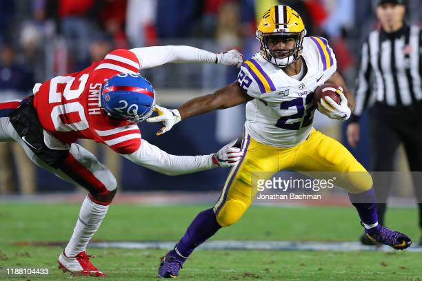 Clyde EdwardsHelaire of the LSU Tigers runs with the ball a Keidron Smith of the Mississippi Rebels defends during the first half of a game at...