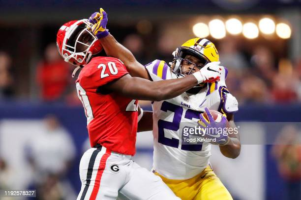 Clyde EdwardsHelaire of the LSU Tigers stiff arms JR Reed of the Georgia Bulldogs in the second half during the SEC Championship game at MercedesBenz...