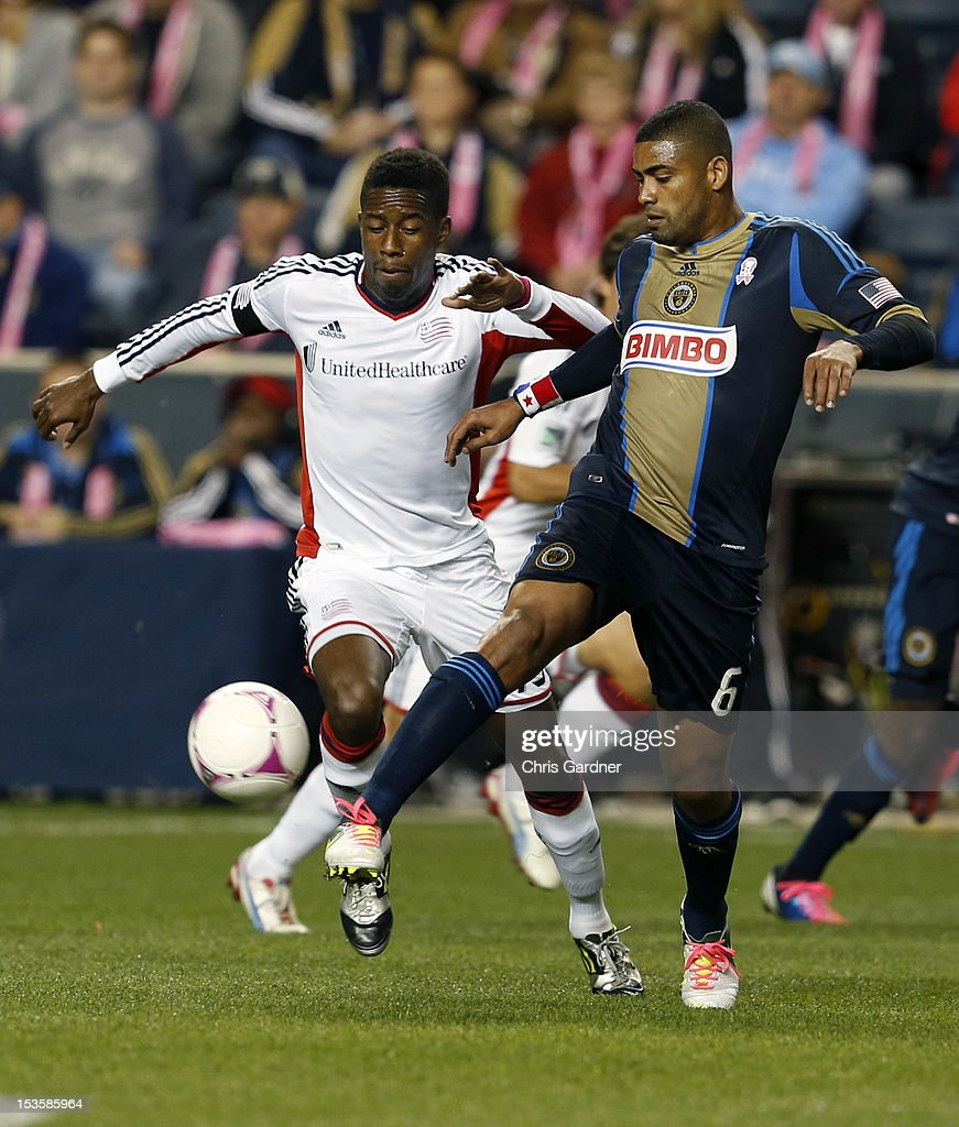 Clyde Simms #19 of the New England Revolution pushes the ball away from Gabriel Gomez #6 of the Philadelphia Union at PPL Park on October 6, 2012 in Chester, Pennsylvania.