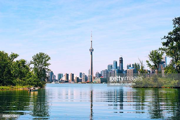 cn tower and skyscrapers by lake ontario against sky - cn tower stock pictures, royalty-free photos & images
