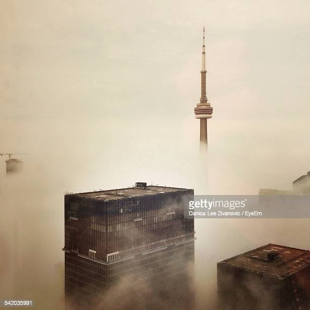 cn tower and skyscrapers covered with fog - cn tower stock pictures, royalty-free photos & images