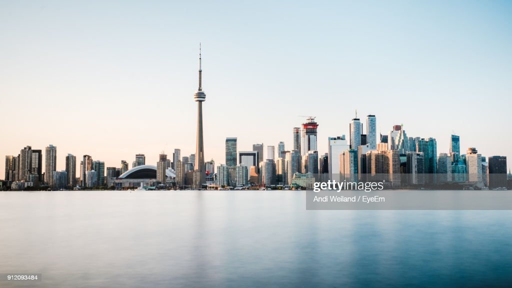 Cn Tower By Lake Against Sky In City : Stock Photo